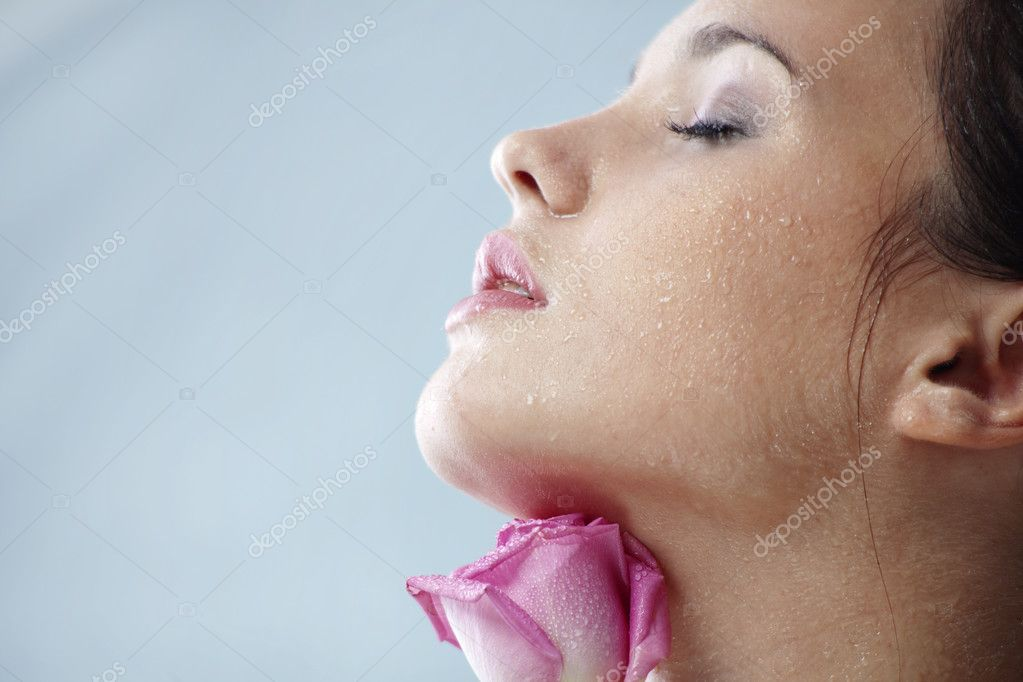 Studio portrait of sensual beautiful woman with rose and water droplets on her face  Foto Stock #2783586