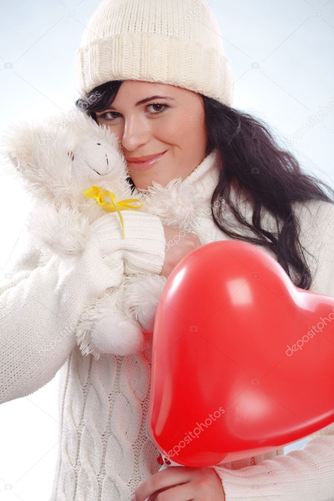 Cute young woman wearing warm winter clothing and holding heart posing in studio — Stock Photo #2783909