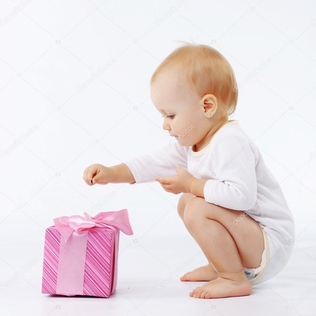 Portrait of child opening gift box in white studio  Foto de Stock   #2784101