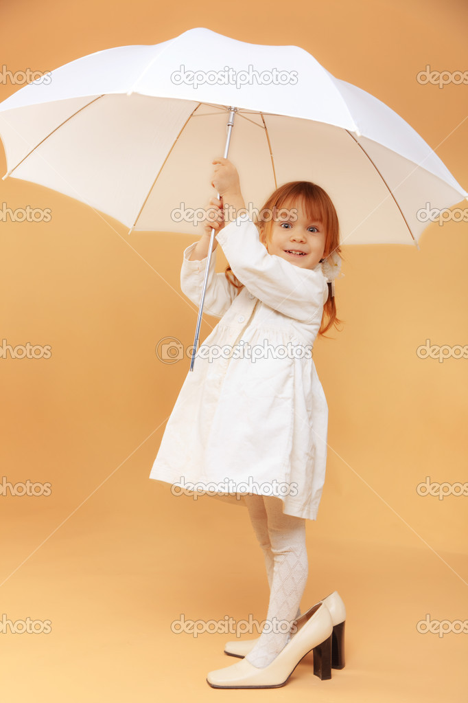 Funny child wearing adult shoes posing with umbrella  Stock Photo #2787082