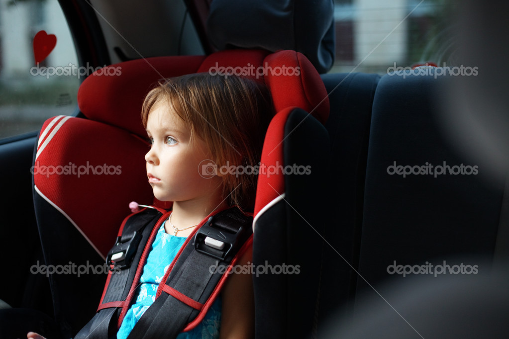 Child in auto baby seat in car looking at window — Stock Photo #2787860