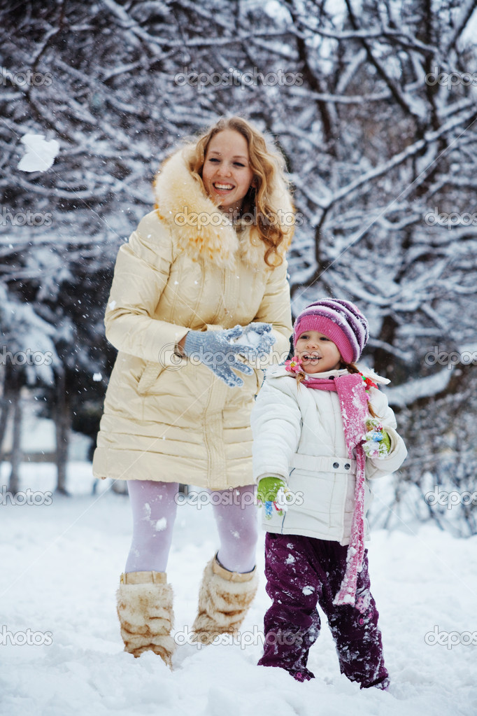 Portrait of young woman with kid girl playing snowballs in winter  Stock Photo #2789180
