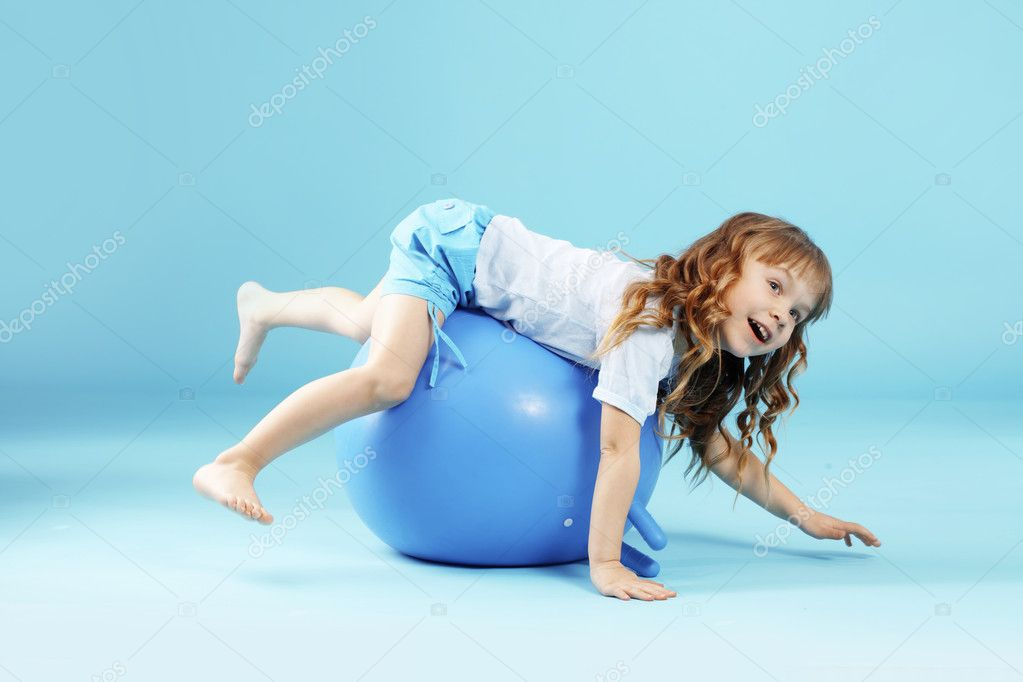 Child with gymnastic ball on bleu studio background — Stock Photo #2791173