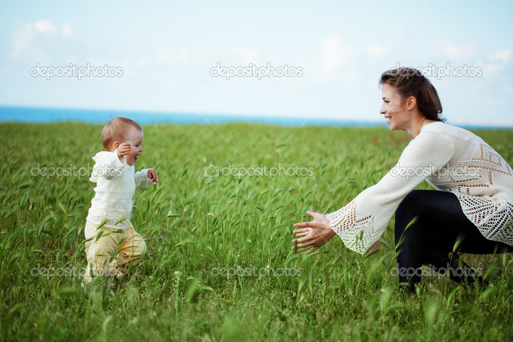 Mother walking with her baby in spring green field — Stock Photo #3163281