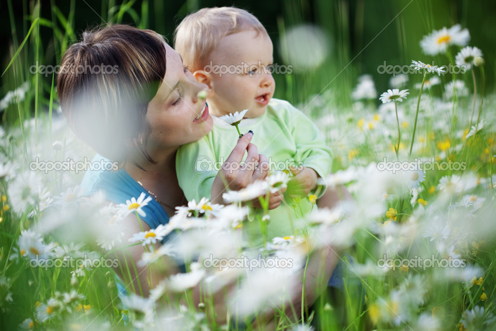 Mother with her child playing in camomile field — Stock Photo #3267475