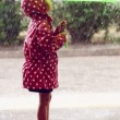 Little girl walking in the rain - Stock Photo