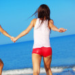 Girls running at beach — Stock Photo #3583361