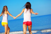 Girls running at beach — Stock Photo