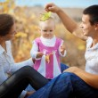 Parents with baby in autumn - Stock Photo