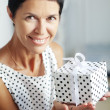 Middle aged woman with a gift — Stock Photo