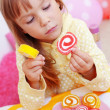 图库照片: Cute child eating candies