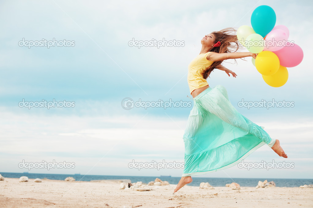 Happy girl holding bunch of colorful air balloons at the beach — Stock Photo #3917168