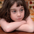 Serious cute little girl rests her head — Stock Photo