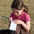 Stock Photo: Cute little girl writes while sitting on grass