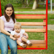 Mother and a child swinging in a playground — Stock Photo