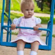 Little girl swinging in a playground — Stock Photo