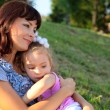 Mother and daughter sit on the grass — Stock Photo