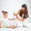 Little girl and her mother blowing bubbles — Stock Photo