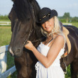 Stock Photo: Young blond woman in white dress with horse