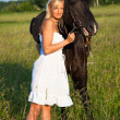 Young blond woman in white dress with horse - Stock Photo