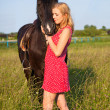 Young blond woman with horse - Stock Photo