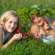 Two young blond women eating strawberries — Stock Photo