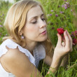 Young blond woman eating strawberries — Stockfoto