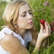 Young blond woman eating strawberries — Stock fotografie
