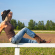 Stock Photo: Young cowgirl sitting on a fence