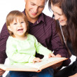 Stock Photo: Mother, fathher and little daughter reading book