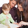 Mother, fathher and little daughter reading book — Foto Stock