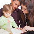 Mother, fathher and little daughter reading book — Stockfoto