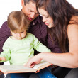 Foto Stock: Mother, fathher and little daughter reading book