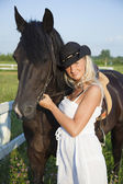 Young blond woman in white dress with horse — Stock Photo