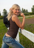 Young cowgirl stand near a fence — Stock Photo