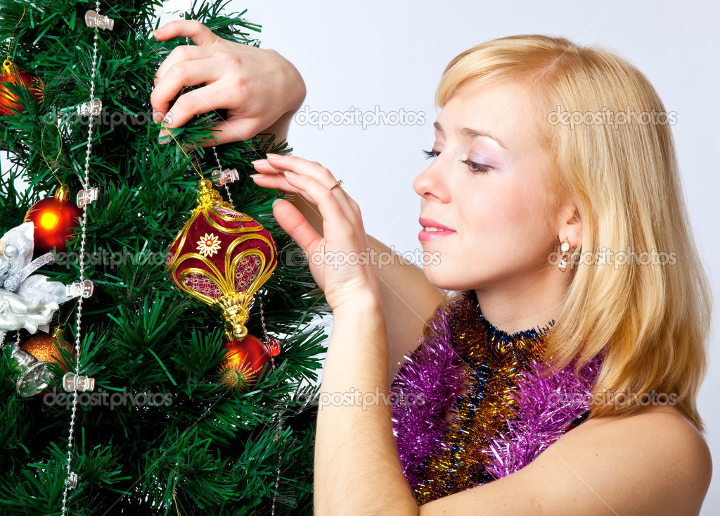 Girl near Christmas fir tree on gray background — Zdjęcie stockowe #4020805