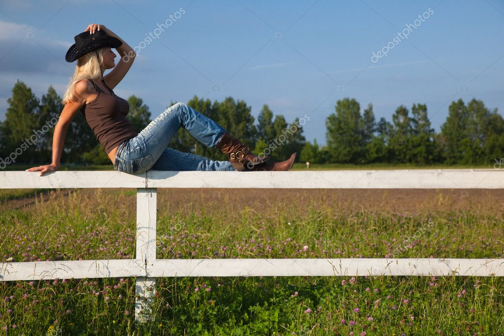 Young cowgirl sitting on a white fence — Stock Photo #4022383