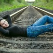 Stock Photo: Young girl lying on railway