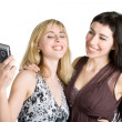 Two teenage girls photographing on mobile phone — Stock Photo