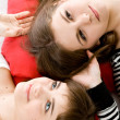 Two girls lying on red pillow — Stock Photo