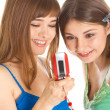 Two pretty girls reading SMS on mobile phone - Stock Photo