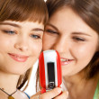 Two pretty girls reading SMS on mobile phone — Stock Photo #4031288