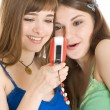 Two pretty girls reading SMS on mobile phone — Stock Photo #4031294