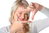Unga blonda kvinnan tittar genom en ram av hennes fingrar — Stockfoto