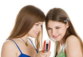 Two pretty girls reading SMS on mobile phone — Стоковое фото
