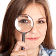 Girl is looking through magnifying glass — 图库照片
