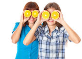 Two girls are looking through oranges — Stock Photo