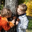Stock Photo: A girl and a boy are playing hide-and-seek