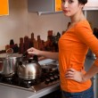 A young woman is putting a kettle — Stockfoto