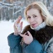 A woman with a figure of a crystal angel is in the winter forres — Stock Photo